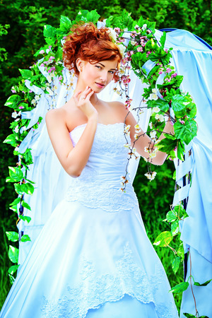 wedding accessories: Beautiful bride with chaming red hair stands under the wedding arch. Wedding dress and accessories. Wedding decoration. Stock Photo
