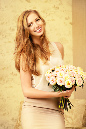 sexy birthday: Beautiful young woman in a room holds a bouquet of roses. Beauty, fashion.