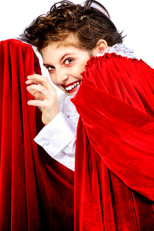 insidious: Expressive teen boy in a costume of vampire posing over white background.  Halloween. Isolated.