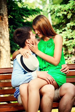 love kissing: Young people tenderly kissing on a park bench. Love concept.