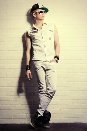 modelos hombres: Moderno joven en ropa de jeans posando junto a la pared de ladrillo blanco. Moda juvenil.