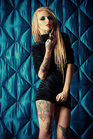 Gothic style: Sexual girl with black make-up and long dreadlocks wearing black dress. Gothic style. Fashion. Cosmetics, hairstyle. Tattoo. Stock Photo