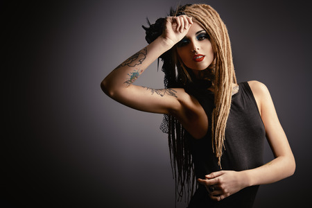 tattoo face: Gorgeous sexy girl with black make-up and long dreadlocks. Gothic style. Fashion. Cosmetics, hairstyle. Tattoo. Stock Photo