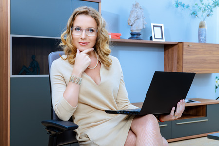 Beautiful business woman sitting on a couch and working on a laptop. photo