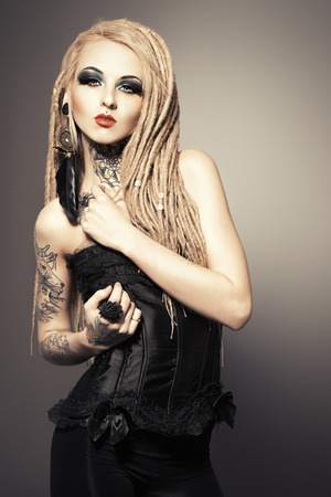 gothic woman: Gorgeous sexy girl with black make-up and long dreadlocks. Gothic style. Fashion. Cosmetics, hairstyle. Tattoo. Stock Photo