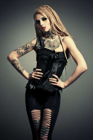 Gothic style: Gorgeous sexy girl with black make-up and long dreadlocks. Gothic style. Fashion. Cosmetics, hairstyle. Tattoo. Stock Photo