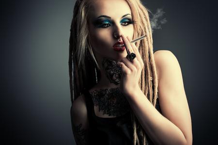 chica fumando: Smoking girl sexy con maquillaje negro y largas rastas. Estilo gótico. Moda. Cosméticos, peinado. Tattoo.