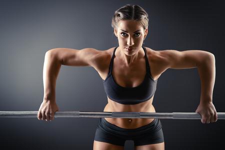 pesas: Mujer joven fuerte con hermoso cuerpo atlético hacer ejercicios con mancuerna. Fitness, culturismo. Cuidado de la salud.