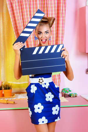 show business: Beautiful pin-up girl on a pink kitchen posing with cinema clapper board. Retro style. Show business. Cinematography. Stock Photo