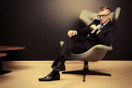 silla: La imposici�n de hombre maduro en traje elegante sentado en una silla de cuero en un interior lujoso y moderno. Moda. Negocio.