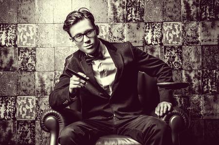 hombre fumando puro: Apuesto joven en traje elegante fumar un cigarro. Él está sentado en una silla de cuero en un interior de lujo. Foto de archivo