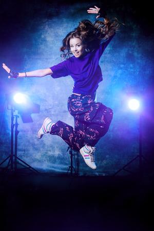 danza contemporanea: Hermosa bailarina de hip-hop saltando sobre fondo grunge. Foto de archivo