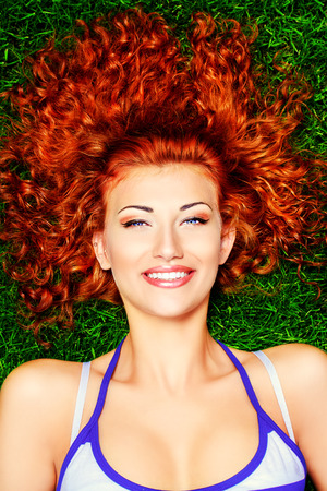 haircare: Close-up portrait of a beautiful curly red-haired girl lying on a green lawn and smiling. Haircare, hairstyle. Stock Photo