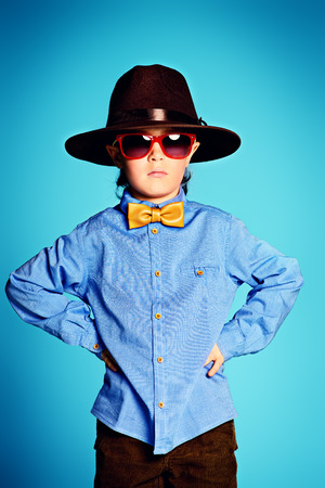 7 year old: Portrait of a cute 7 year old boy wearing elegant hat and bow-tie with sunglasses.