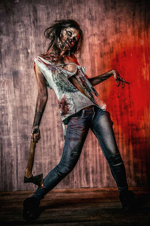 zombie: Scary bloody zombie girl with an ax. Halloween.