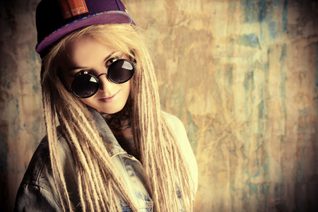 modern generation: Modern teenage girl with blonde dreadlocks over grunge background. Jeans style. Modern generation.