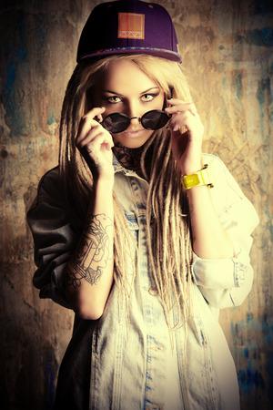 modern generation: Adolescente moderna con rastas rubias sobre el fondo del grunge. Estilo Jeans. Generaci�n moderna. Foto de archivo