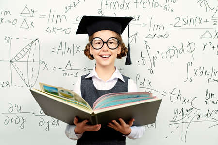 onderwijs: Behoorlijk slim schoolmeisje in grote glazen en academische hoed stands met geopende boek op het schoolbord. Onderwijs.