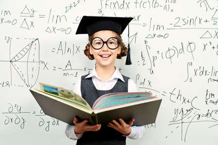education: Écolière très intelligent dans de grosses lunettes et porte-chapeaux académiques avec livre ouvert sur le tableau noir. Éducation.