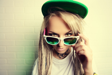 modern generation: Modern teenage girl with blonde dreadlocks standing by the brick wall. Jeans style. Modern generation.