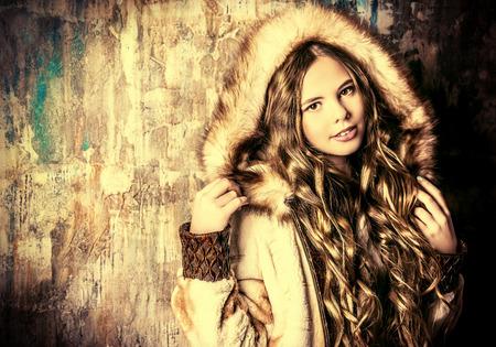 ringlet: Fashion shot of a pretty teenager girl with beautiful long curly hair wearing fur coat. Beauty, fashion.