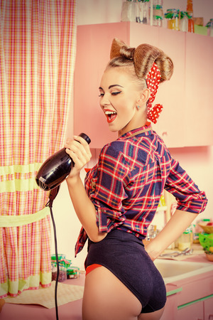 hair bow: Beautiful pin-up girl doing a hair with a hair dryer and comb on her pink kitchen. Retro style. Fashion.