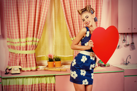 retro housewife: Lovely pin-up girl stands on a pink kitchen and holds a big red heart. Retro style. Love concept.