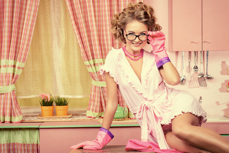 alluring: Sexy pin-up girl wearing pink bathrobe alluring on her pink kitchen at home. Fashion.