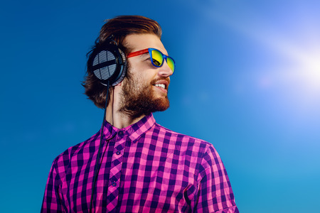 sexy headphones: Portrait of a dreamy handsome young man listening to music in headphones. Blue sky background. Leisure, summer, vacation.