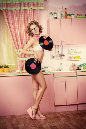 sexy housewife: Pretty girl in sexy lingerie alluring with vinyl records on her glamorous pink kitchen. Fashion. Pin-up style.