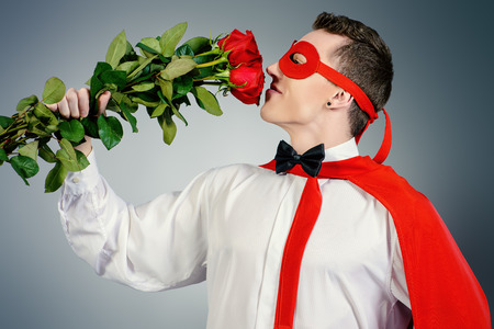 creative force: Young handsome man in a superhero costume holding a bouquet of red roses. Love concept. Stock Photo