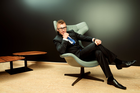 Imposing mature man in elegant suit sitting on a leather chair in a modern luxurious interior. Fashion. Business. Stock Photo