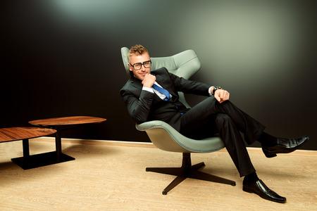 traje formal: La imposici�n de hombre maduro en traje elegante sentado en una silla de cuero en un interior lujoso y moderno. Moda. Negocio.