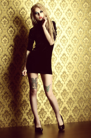gothic woman: Attractive sexy girl with black make-up and long dreadlocks standing by the vintage wall. Gothic woman. Fashion. Cosmetics, hairstyle. Tattoo.