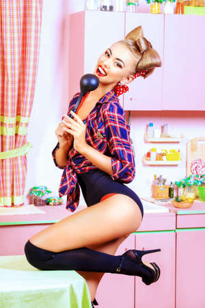ladle: Attractive pin-up girl cooking on her pink kitchen. Retro style. Fashion. Stock Photo