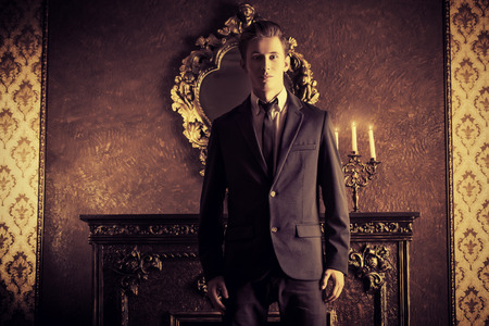 suit: Handsome respectable man in elegant suit stands in a room with classic vintage style. Business. Fashion.