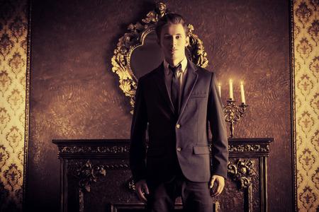 traje formal: Hombre respetable hermoso en juego elegante se encuentra en una habitaci�n con el estilo cl�sico de la vendimia. Negocio. Moda.