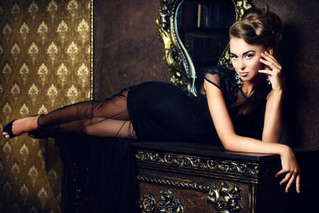 Elegant young woman in black evening dress posing in vintage interior. Fashion shot.
