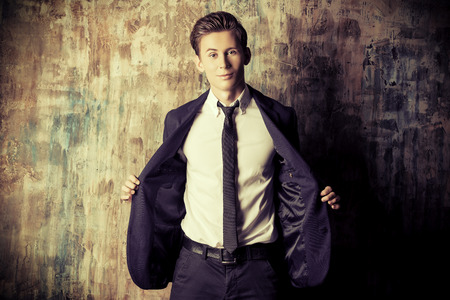 charm: Portrait of a handsome young man in elegant suit standing over grunge background. Stock Photo