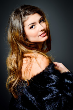 magnificent: Close-up portrait of a magnificent young woman wearing fur jacket. Studio shot. Beauty, fashion. Make-up, cosmetics.