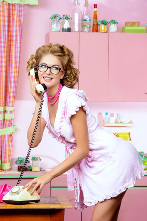 Beautiful sexy pin-up girl talking on the phone on a pink kitchen. Fashion. photo