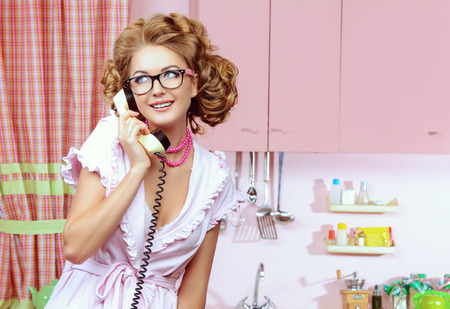 sexy housewife: Beautiful sexy pin-up girl talking on the phone on a pink kitchen. Fashion.