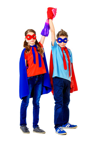 supergirl: Boy and girl teenagers in a costume of superheroes posing together. Isolated over white background.