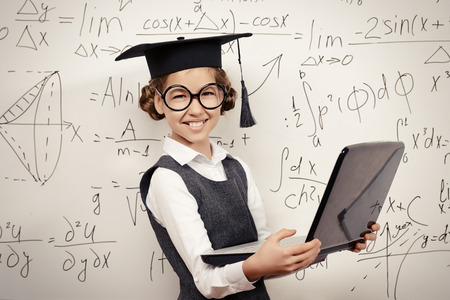 schoolgirl in uniform: Smiling smart schoolgirl in big glasses and academic hat performs the task at the blackboard with a laptop. Education.