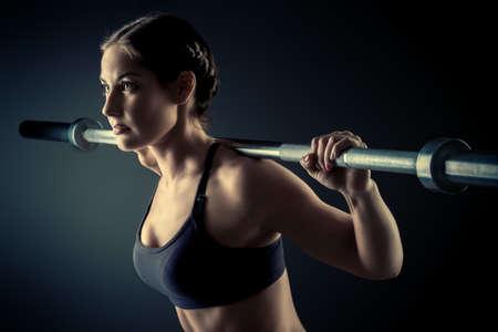 Sterke jonge vrouw met mooie atletisch lichaam doet oefeningen met barbell. Fitness, bodybuilding. Gezondheidszorg.