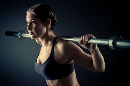 sport training: Strong young woman with beautiful athletic body doing exercises with barbell. Fitness, bodybuilding. Health care.