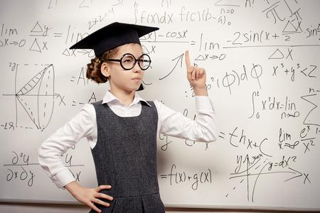 schoolgirl uniform: Happy smart schoolgirl in big glasses and academic hat performs the task at the blackboard. Education. Stock Photo
