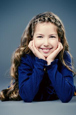 cabello largo y hermoso: Retrato de una muchacha adolescente bonita con el pelo largo y hermoso sonriendo a la c�mara. Estudio de disparo.