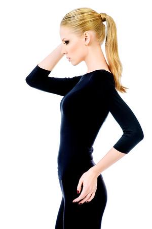 cuerpo femenino perfecto: Hermosa modelo de mujer delgada en ropa ajustada negro posando sobre fondo blanco. Belleza, la moda. El cuidado del cuerpo. Aislado en blanco. Foto de archivo