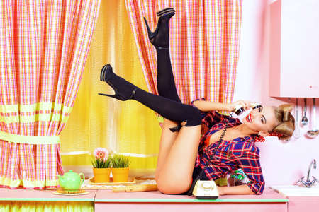 pin-up girl talking on the phone on a pink kitchen. Retro style Fashion.